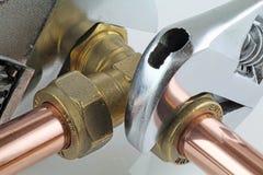 Plombier serrant la canalisation Photographie stock libre de droits