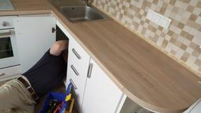 Plombier travaillant à la cuisine banque de vidéos