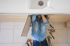Plombier travaillant avec la tuyauterie cass?e et disjointe de cuisine image stock