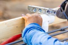 Plombier Using Level While installant le tuyau de PVC au chantier de construction image libre de droits