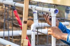 Plombier Using Level While installant le tuyau de PVC au chantier de construction images stock