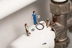 Plombiers miniatures réparant un thermostat Photo stock