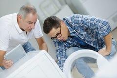 Plombiers réparant la machine à laver image libre de droits