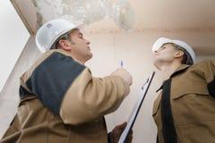 Plombiers vérifiant le problème dans le plafond photos libres de droits