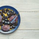 Plommoner och blåbär i en platta royaltyfri foto