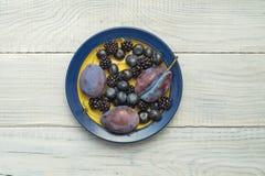 Plommoner och blåbär i en platta fotografering för bildbyråer