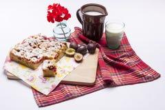 Plommonkakan och koppen av mjölkar på vit. arkivbilder