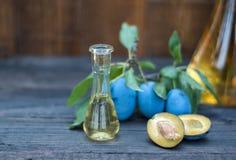 Plommonkonjak eller brännvin med ny och smaklig plommonfrukt Royaltyfri Foto