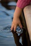 Plongement des doigts dans l'étang Image libre de droits