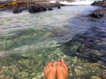 Plongement des pieds dans la piscine de marée en Hawaï Photo stock