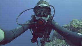 Plongeur autonome d'homme de portrait dans les bulles d'air de soufflement de réservoir de masque et de plongeur sous la mer banque de vidéos