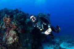 Plongeur autonome sur un récif foncé Photos stock