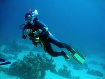 Plongeur avec l'appareil-photo dedans profond Photographie stock libre de droits