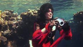 Plongeur libre de modèle de jeune fille sous-marin dans le costume rouge du pirate en Mer Rouge banque de vidéos