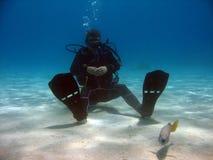 Plongeur s'asseyant sur le sable Images stock