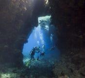 Plongeurs autonomes dans une caverne sous-marine Image libre de droits