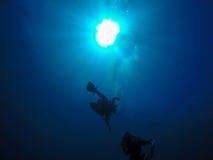 Plongeurs autonomes et bulles d'air contre la lumière du soleil Image stock