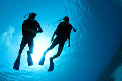 Plongeurs autonomes silhouettés Photographie stock