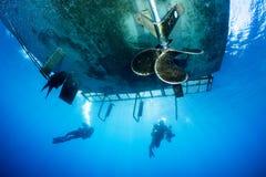 Plongeurs autonomes sous le bateau de piqué Images libres de droits