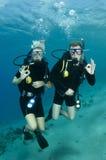 Plongeurs autonomes sur un piqué photographie stock libre de droits