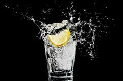 Plons in een glas met citroen en ijs op zwart ba Stock Foto