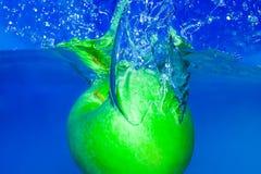 Plons-serie-bespat: groene appel met blauwe achtergrond Stock Foto's