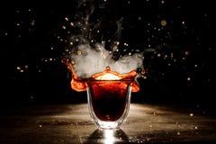Plons van de koffie van het transparante glas op de donkere achtergrond Royalty-vrije Stock Fotografie