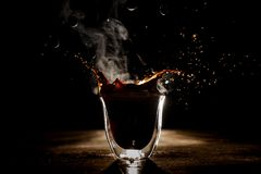 Plons van de koffie in het transparante glas op de donkere achtergrond Royalty-vrije Stock Fotografie