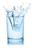Plons van ijsblokje in een glas water. Stock Fotografie