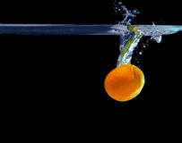 Plons van mandarijn in water Het concept van de versheid Stock Foto's