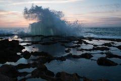 Plons van oceaangolven tegen een achtergrond van zonsondergang en rotsen royalty-vrije stock afbeeldingen