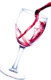 Plons van rode die wijn in glas op wit wordt geïsoleerd Stock Fotografie