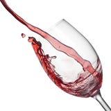 Plons van rode wijn in wijnglas op wit royalty-vrije stock afbeeldingen