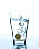 Plons van water en muntstukken in een glas Royalty-vrije Stock Foto's
