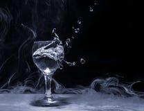 Plons van water van een glas Stock Foto's