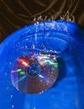 Plons in water bij dalende CD schijf stock foto's