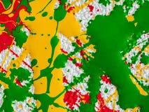 Plonsen van rode en geelgroene verf op een witte achtergrond royalty-vrije stock foto