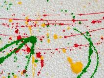 Plonsen van rode en geelgroene verf op een witte achtergrond stock foto