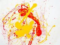 Plonsen van rode en gele verf op een witte achtergrond stock afbeelding