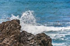 Plonsen van water het breken op rotsen Royalty-vrije Stock Foto