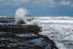 Plonswater van de oceaan, klip, blauwe hemel, Nieuw Zeeland royalty-vrije stock afbeeldingen