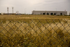 Plot of land. In North Greece surrounded with fence, yellow grass , summer Royalty Free Stock Photo