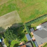 Plots with a meadow, a lawn, a detached house and a terraced house adjoin at one point, plot boundaries look like an abstract cros. S, Germany Stock Images