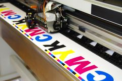 Plotter head printing CMYK. Test on white paper. Digital large inkjet machine working royalty free stock images