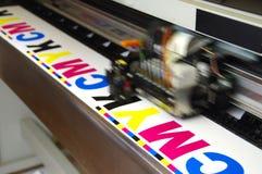 Plotter head printing CMYK. Test on white paper. Digital large inkjet machine working stock image