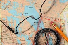 Plotting a journey. Glasses, map and compass Stock Image