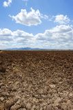 Plough plowed brown clay field blue sky horizon Stock Images