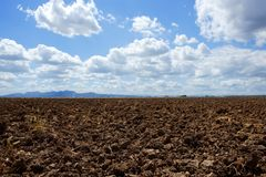 Plough plowed brown clay field blue sky horizon Royalty Free Stock Photos