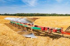 Plough ready to work on stubble field Stock Photos