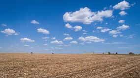 Ploughed cultivated ground, field and cloudy blue sky. Ploughed cultivated ground, field against cloudy blue sky royalty free stock photography